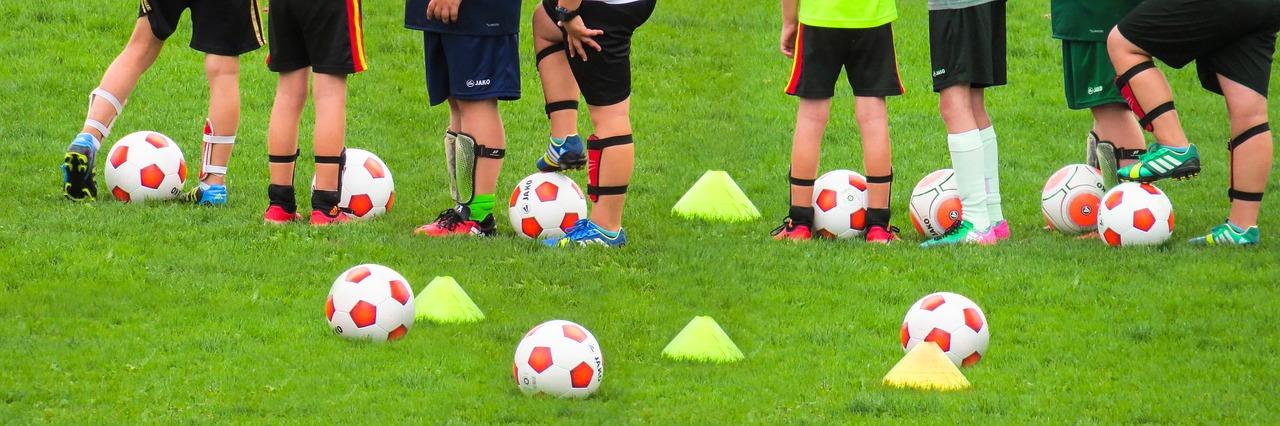 Aufwärmen im Kinderfußball, eine Gruppe Kinder mit Fußbällen